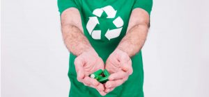 Image of man in green shirt holding batteries